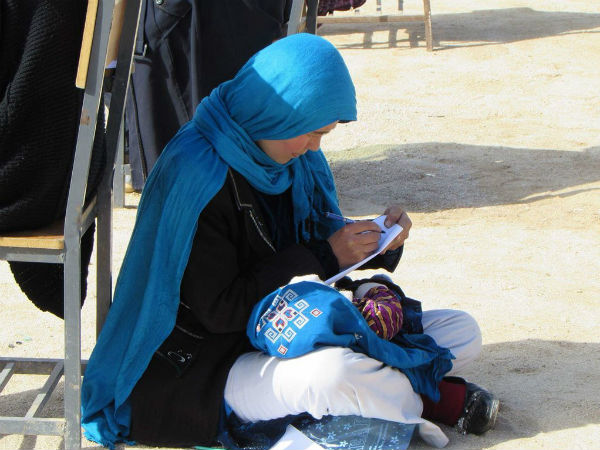 V25 Year Old Afghan Woman Takes Exam While Nursing Her Baby